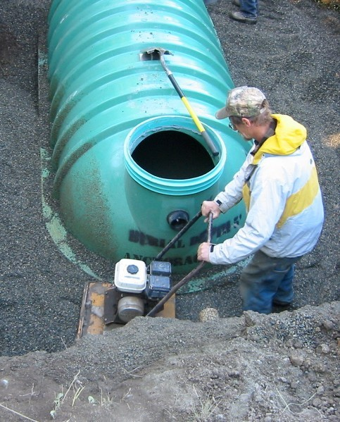 Compacting fill around a septic tank.